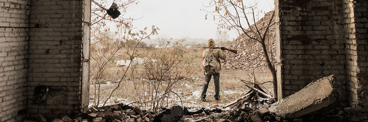 Boy with rifle stands in post-conflict remains of building