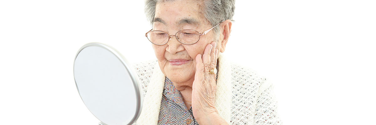 Elderly lady holds a mirror in front of her face and touches her face with the other hand