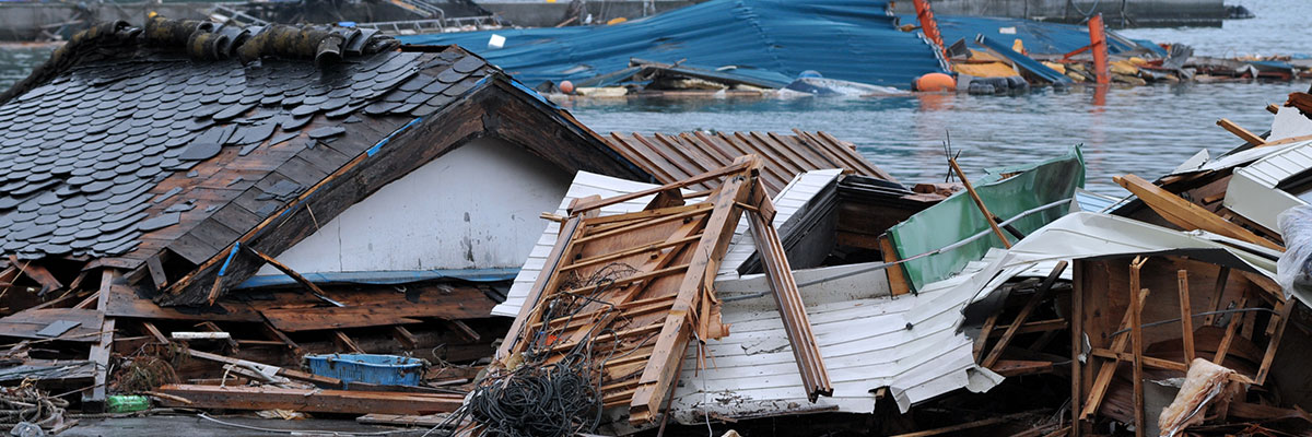 Mostly wooden debris from a tsunami piled up next to a damaged building