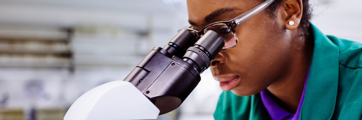 researcher-looking-down-microscope