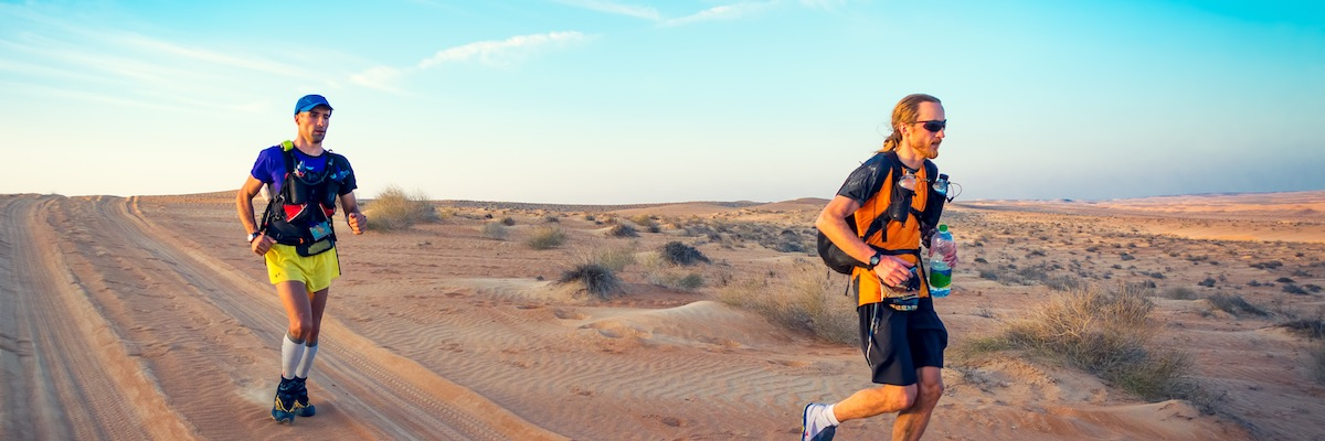 Two runners competing in extreme heat in the desert