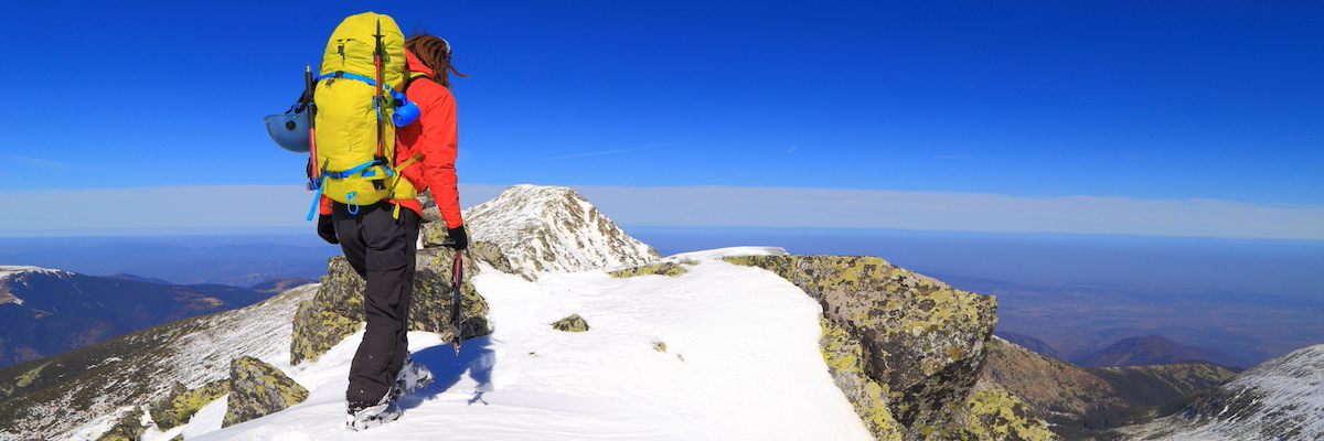 Hiker climbing snowy mountain with heavy backpack