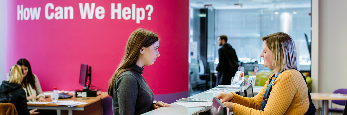 Female student standing at careers and employability help desk