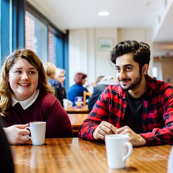 Male and female University of Portsmouth students drinking coffee