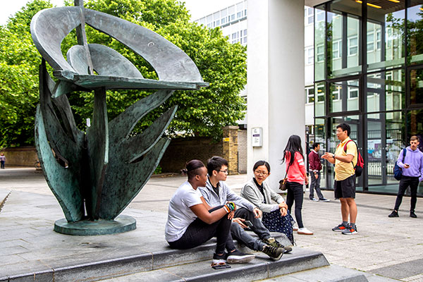 A group of young people sitting outdoors by a public sculpture