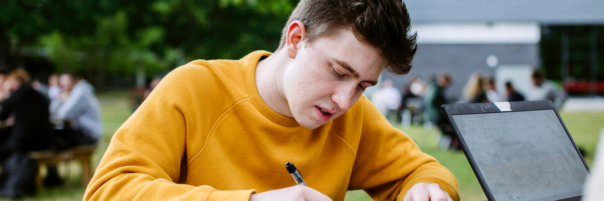 Student studying outside in yellow jumper