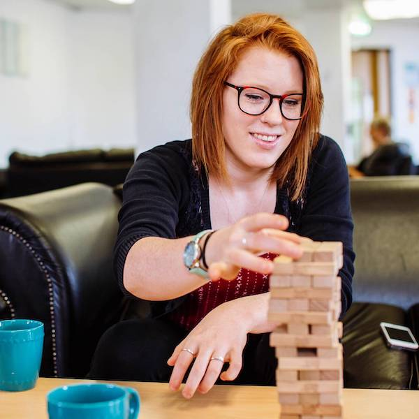 Student playing jenga in halls