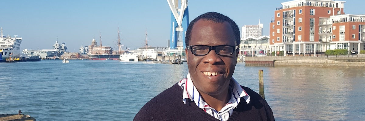 Headshot of Andrew Nomoja in front of the Spinnaker Tower in Portsmouth Harbour