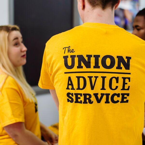Student Union staff members giving advice in yellow t-shirt