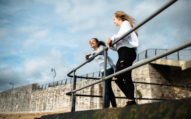 Two female students in Old Portsmouth, resting on railing