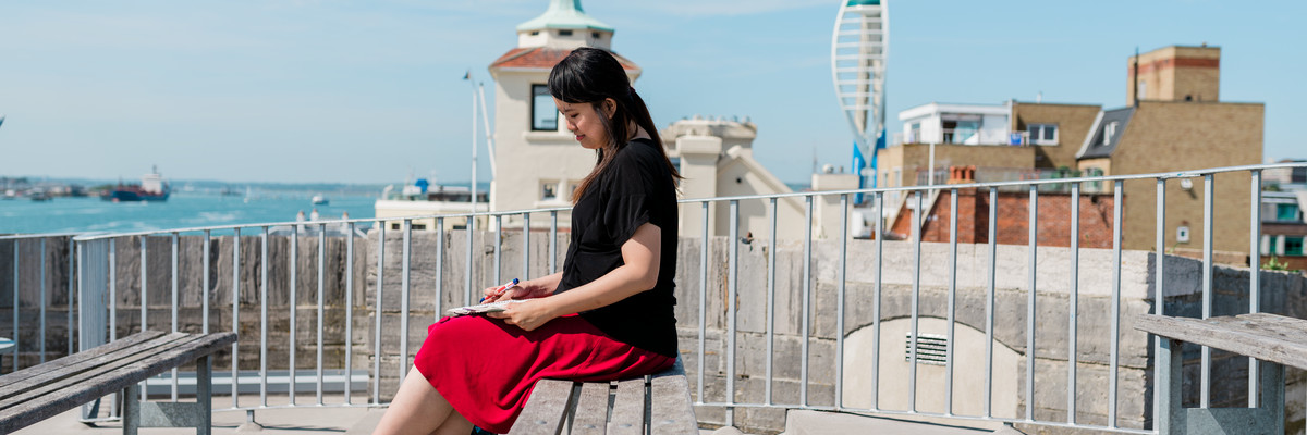 A woman seated on a bench in Old Portsmouth