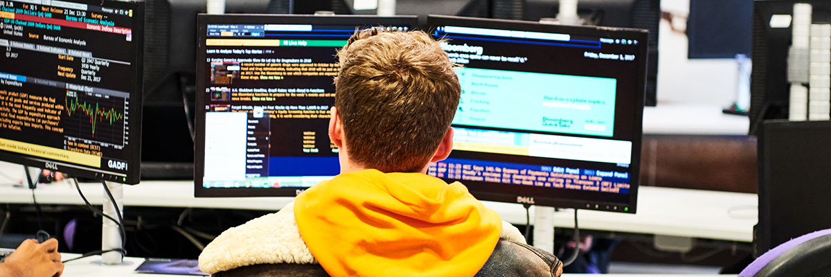 Colombian student sitting at stock trading computer