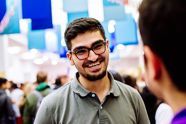 Young man with beard and glasses smiling at an event