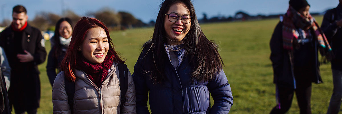 female student from malaysia walking on southsea common with friends