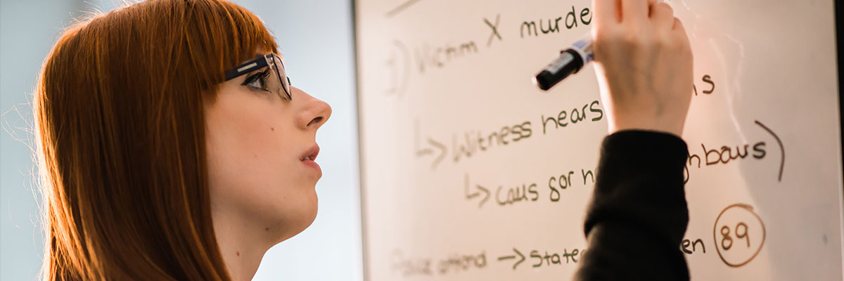 female student from the republic of ireland writing on whiteboard