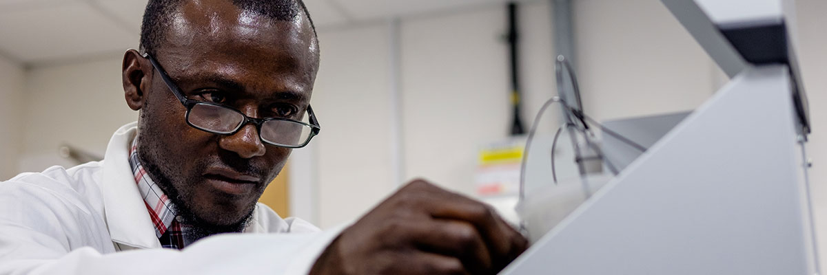male student from senegal adjusting biology equipment