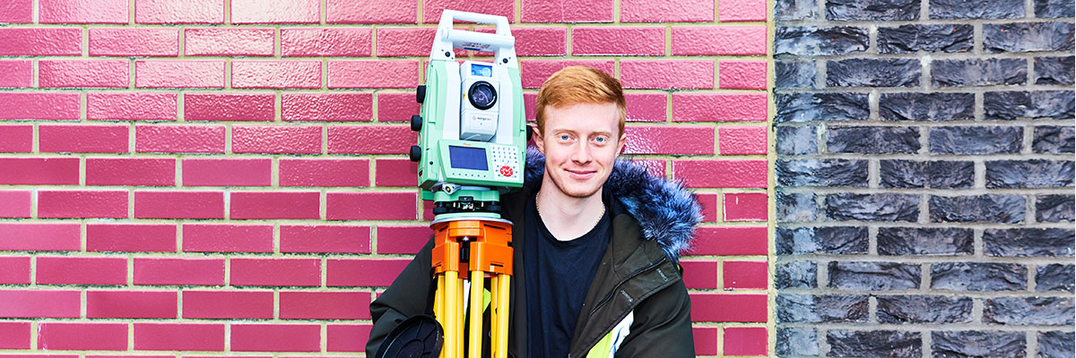 male student holding surveying equipment