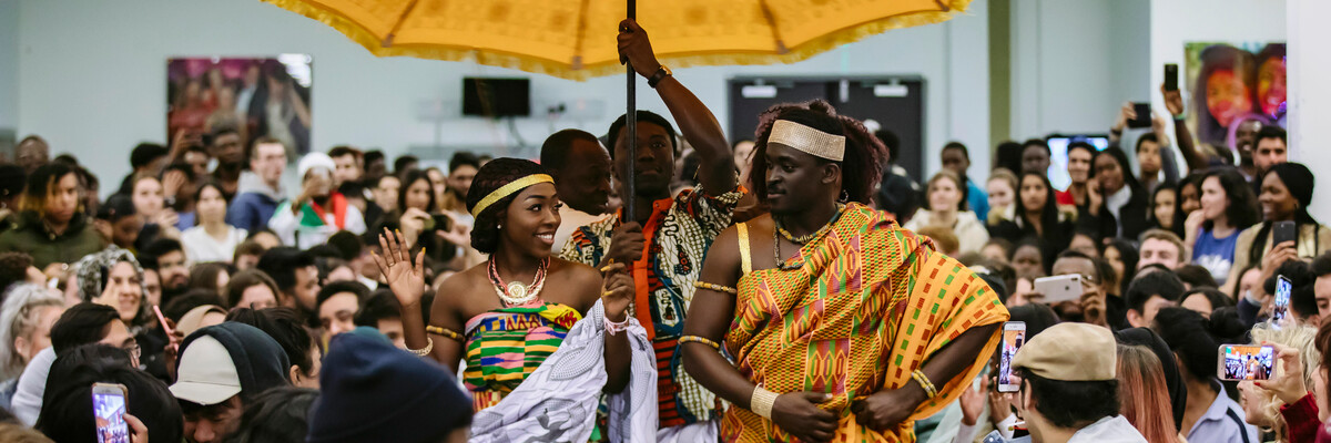 woman and man wearing traditional Ghanaian dress in crowd