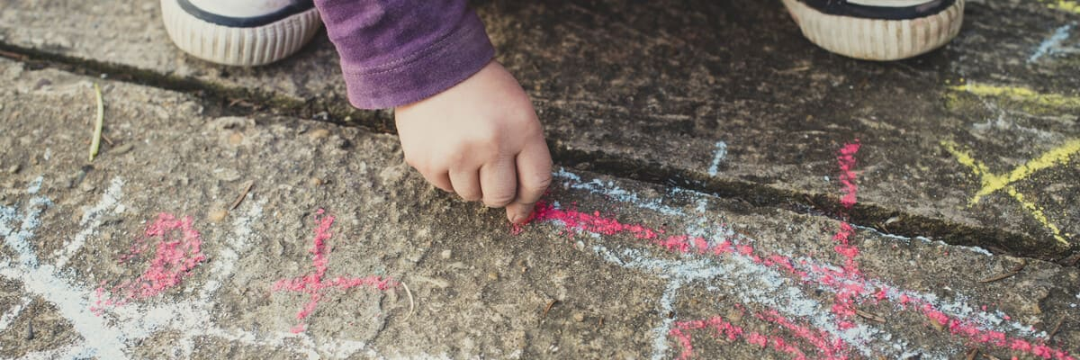Child crouched and drawing on pavement with chalk
