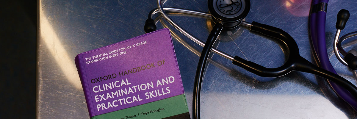 Medical text book and stethoscope on metal table