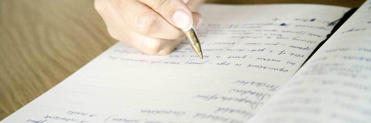 Hand writing in open, non-ruled notebook