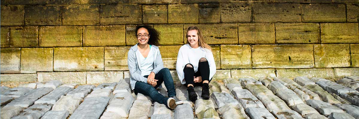 2 students sat at sea wall in Old Portsmouth