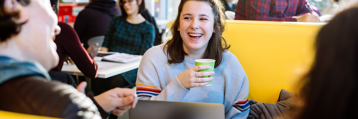 Students laughing with coffee on yellow sofas
