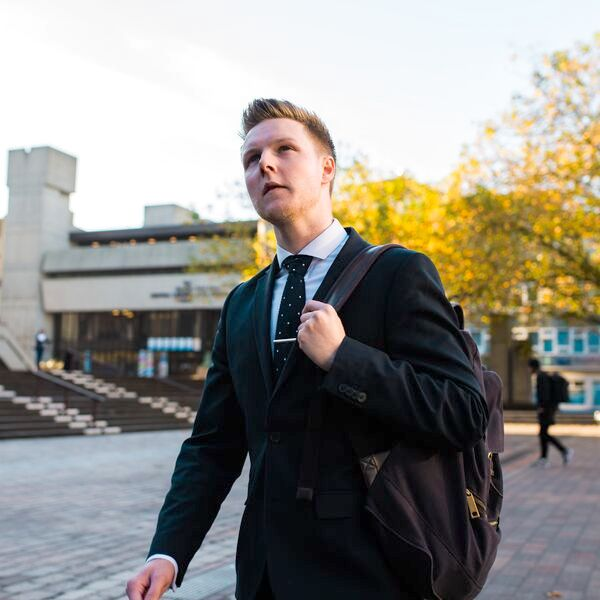 Male University of Portsmouth graduate in suit, with backpack