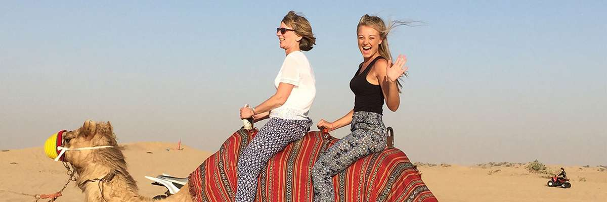 Abbi Mullan and companion riding a camel in a desert
