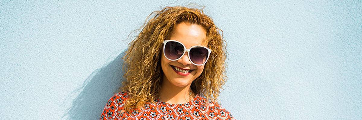 Angelica with large sunglasses, smiling, against a blue background