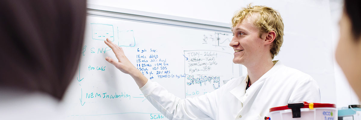 Man in lab coat explaining something and gesturing to whiteboard