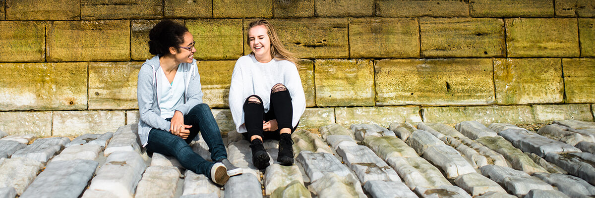 Two students laughing and sitting on a roof in front of a yellow brick wall