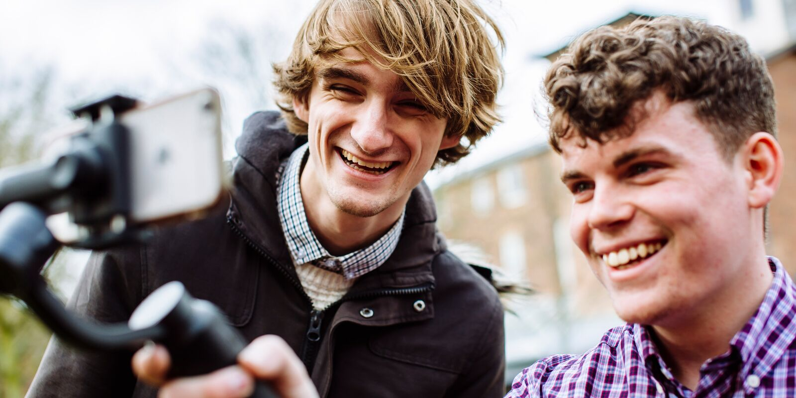 2 students smiling back a smartphone on selfie-stick