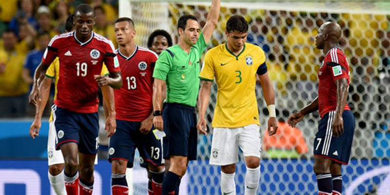 Referee holding yellow card in front of group of players