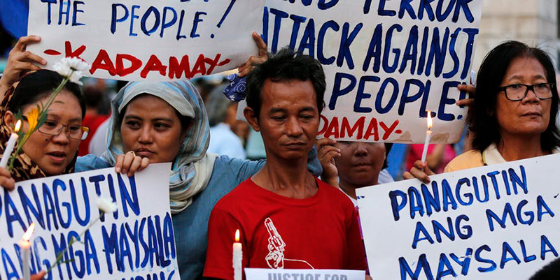 Filipinos holding signs and candles during a protest