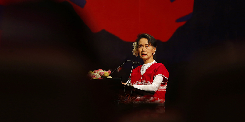 Aung San Suu Kyi wearing red clothing speaking in front of microphones