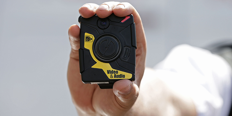man wearing uniform holding a black and yellow body camera