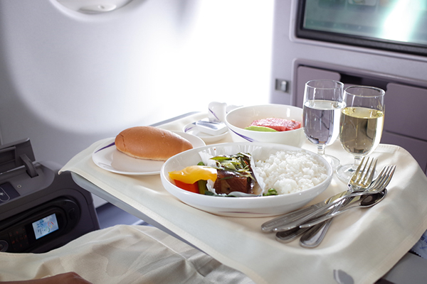 Plates of food and drinks on a tray at the seat of an airplane passenger