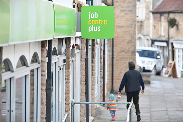 Man and child walking past a job centre plus, holding hands