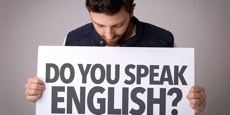 Man holding sign saying 'do you speak English?'