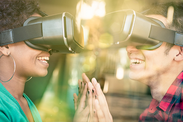 Man and woman wearing virtual reality headsets, smiling and touching hands