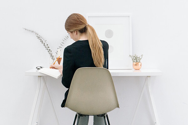 A person sitting at a computer desk writing in a notebook