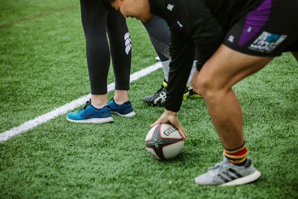 Rugby player holding down ball on pitch
