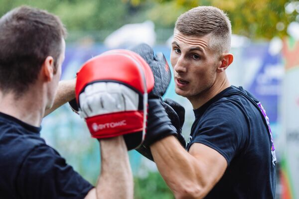 Two male students practice boxing at freshers' fair