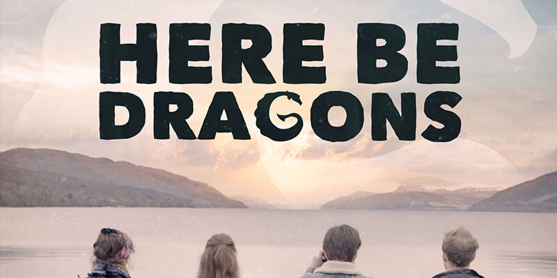 Two women and men, with their backs to the camera, looking out to the sun setting on a mountainous horizon, with text displaying 'Here Be Dragons' above