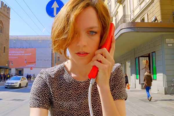 Woman on street listening to red telephone