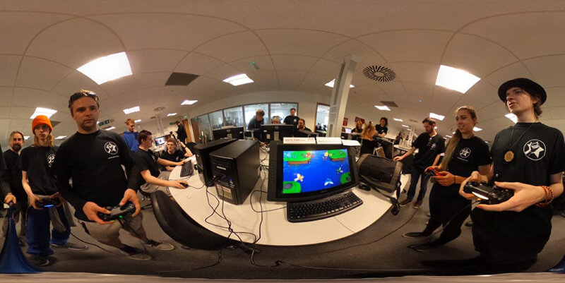 A 360 panorama of people in black GameJam T-shirts, playing video games at white workstations