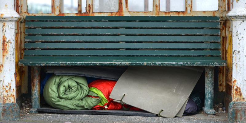 Homeless belongings under bench