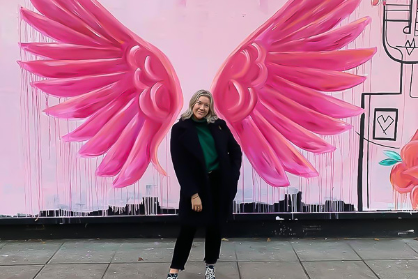 Female student in front of pink wall painting