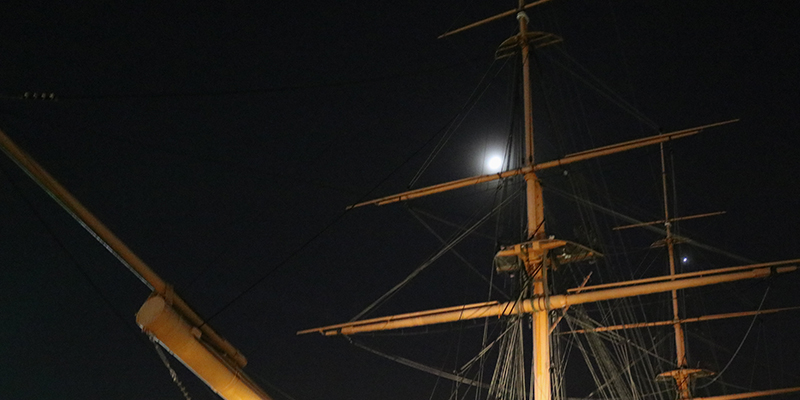 HMS Warrior at night, with moon visible near the central mast